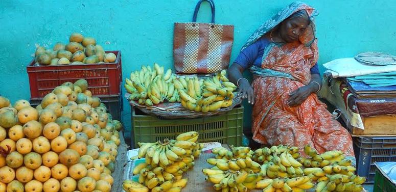 lady-sleeping-at-banana-stand-india