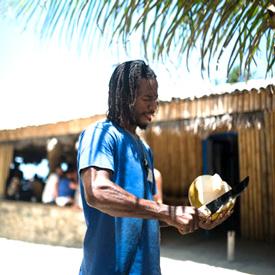 Jamaican man cutting a coconut