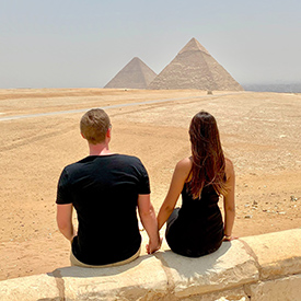 couple sitting at pyramids in egypt