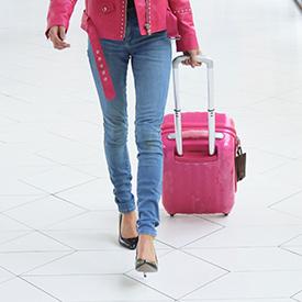 Minimalist woman pulling small luggage