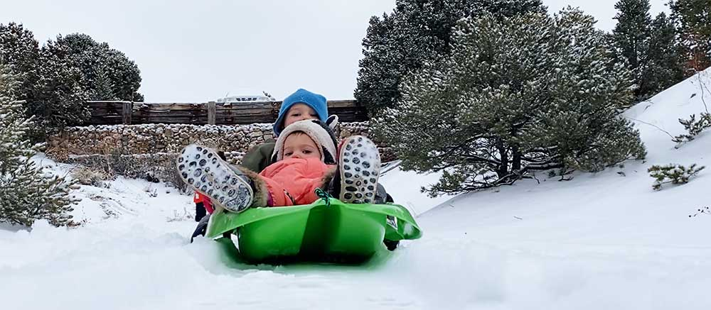 kingsley and aurora sledding in the snow