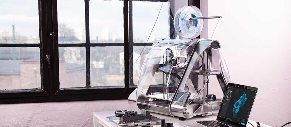 3D Printer on a desk next to a laptop