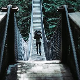 Woman crossing bridge