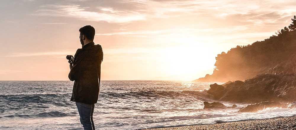 Man vlogging by the ocean