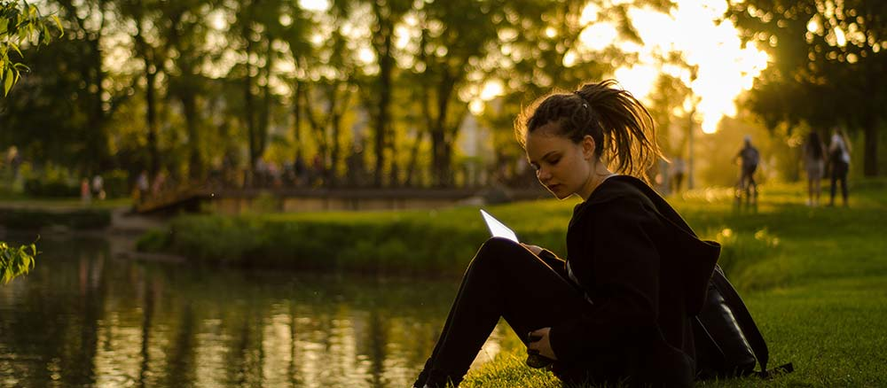 Girl studying by a pond